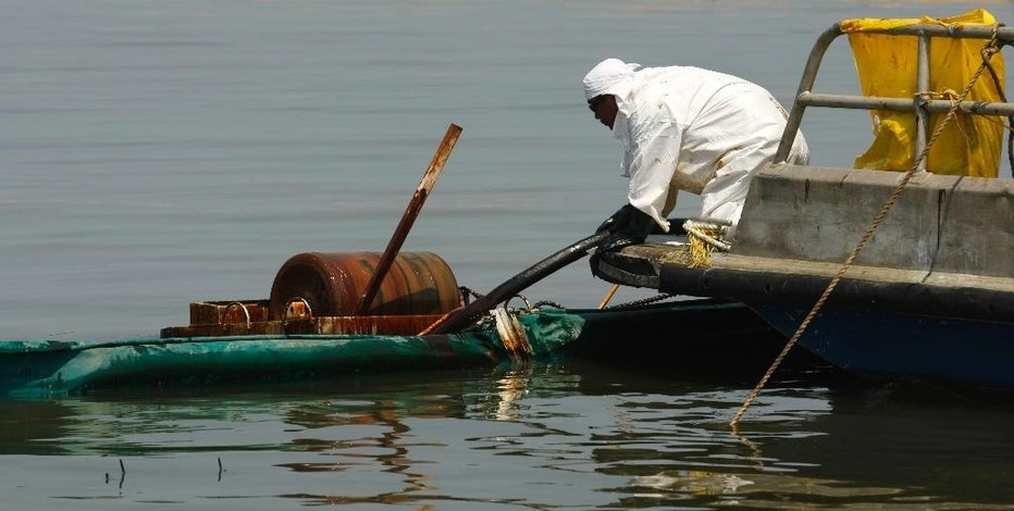 FILE - In this May 24, 2010, file photo, a contractor operates an oil skimmer near a marsh impacted from the Deepwater Horizon oil spill in Pass a Loutre, La. Environmental activists Karen Savage and Cherri Foytlin wrote an article criticizing a company that published a study finding no connection between chemicals released by the explosion and health problems reported by some cleanup workers. Massachusetts' highest court will hear arguments Oct. 7, 2016, in a bid by Savage and Foytlin to throw out a defamation lawsuit filed by the company, siting a state law that protects citizens exercising their free speech rights. (AP Photo/Gerald Herbert, File)