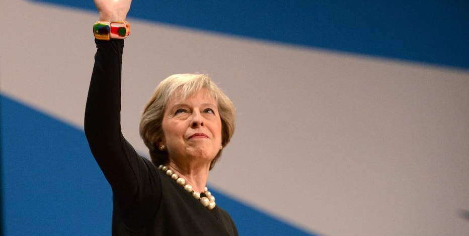 Britain's Prime Minister Theresa May waves to part members assembled to hear her speech at the Conservative Party Conference in Birmingham, England, Sunday Oct. 2, 2016.  Britain will trigger the formal process for leaving the European Union before April 2017, May said Sunday, putting to rest weeks of speculation on the timing of the move. (Ben Birchall / PA via AP)