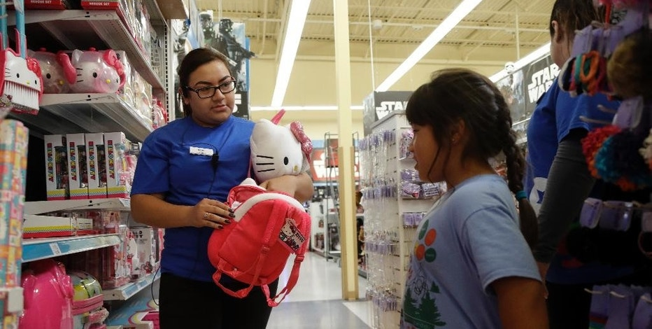 In this Friday, Sept. 30, 2016, photo, Mitzi Solorio, a former seasonal employee now working full time, helps out a customer at a Toys R Us store in San Jose, Calif. Retailers are dangling lots of incentives to lure temporary holiday workers in a tight labor market. That includes increased pay, additional discounts and more flexibility in schedules. (AP Photo/Marcio Jose Sanchez)