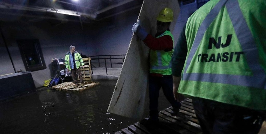 New Jersey Transit workers lay down pallets and boards for commuters to walk on a flooded hallway adjacent to the site of a train crash at the Hoboken Terminal, Friday, Sept. 30, 2016, in Hoboken, N.J. Commuters are using alternative travel in and out of Hoboken a day after a commuter train crashed into the rail station, killing one person and injuring more than 100 people. (AP Photo/Julio Cortez)