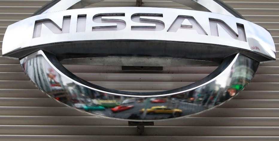 FILE - In this Wednesday, Feb. 8, 2012, file photo, vehicles are reflected on the logo of the Nissan Motors Co. at a showroom in Tokyo's Ginza shopping district. The government is investigating complaints that side air bags on some Nissan Versa small cars can inflate if the driver or passenger doors are slammed too hard. The National Highway Traffic Safety Administration said Tuesday, Oct. 4, 2016, that the probe covers about 155,000 cars from the 2012 model year. (AP Photo/Shizuo Kambayashi, File)