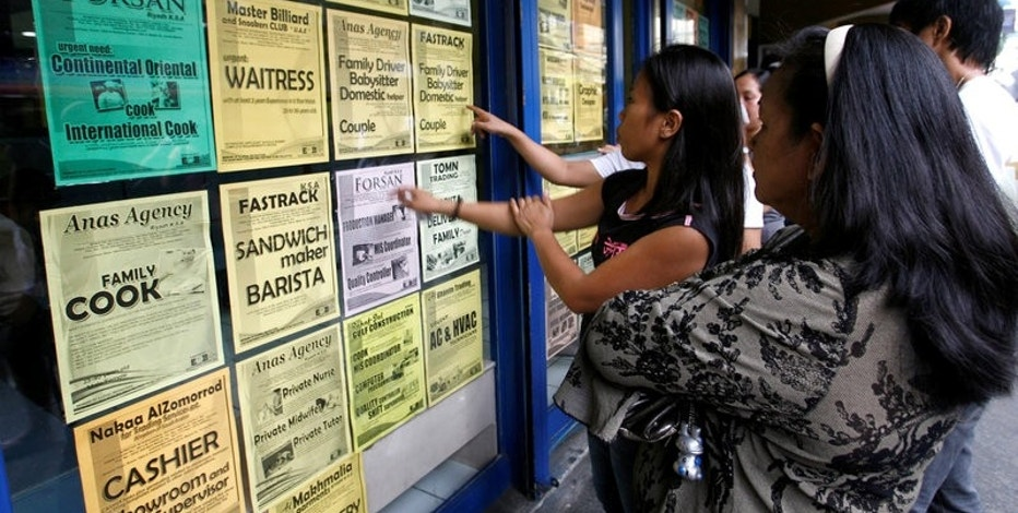 Applicants look at job offers displayed on a glass window of a recruitment agency in Manila in this October 9, 2010 file photo.   REUTERS/Cheryl Ravelo/File Photo