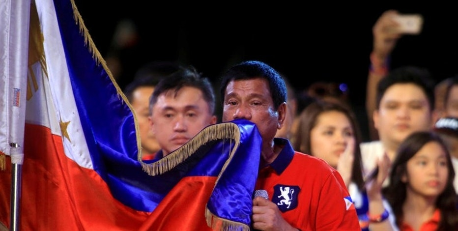 """Philippine presidential candidate and Davao city mayor Rodrigo 'Digong' Duterte kisses the Philippine flag during a """"Miting de Avance"""" (last political campaign rally) before the national elections at Rizal park in Manila in the Philippines May 7, 2016. REUTERS/Romeo Ranoco/File Photo"""