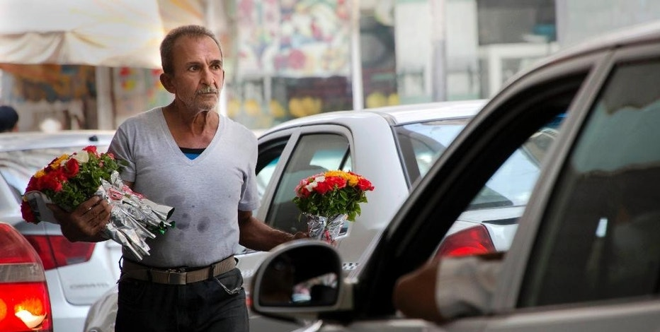 FILE - In this Wednesday, Aug. 17, 2016, file photo, an Egyptian flowers vendor looks for clients at a traffic light in Cairo, Egypt, Wednesday, Aug. 17, 2016. Egypt held its currency steady against the dollar on Tuesday, as it moves ahead with a reform program expected to weaken the pound drastically but also hopefully pave the way for sustainable economic growth that creates jobs for a surging population.  (AP Photo/Amr Nabil, File)