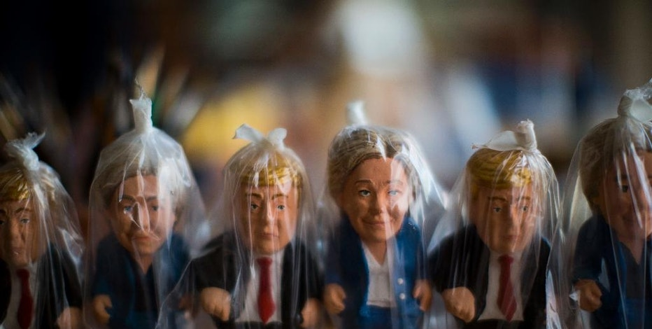 "In this Monday, Oct. 3, 2016 photo, miniatures of U.S. presidential candidates Hillary Clinton and Donald Trump are wrapped in plastic bags in a ""caganer"" factory at Torroella de Montgri, northeast Catalonia, Spain.  A curious Christmas tradition in the Spanish autonomous region of Catalonia depicts both candidates in a rather scatological situation. The miniatures called ""Caganer"", depict a person defecating, and traditionally symbolizes fertilization and a source of luck and prosperity in the new year. (AP Photo/Emilio Morenatti)"