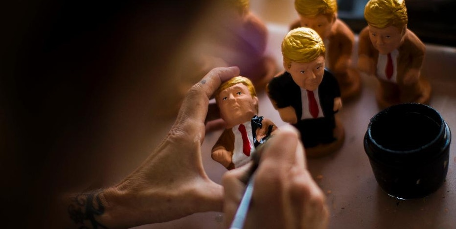 "In this Monday, Oct. 3, 2016 photo, an artisan paints a clay miniature of Donald Trump in a ""caganer"" factory at Torroella de Montgri, northeast Catalonia, Spain. A curious Christmas tradition in the Spanish autonomous region of Catalonia depicts both candidates in a rather scatological situation. The miniatures called ""Caganer"", depicts a person defecating, and traditionally symbolize fertilization and a source of luck and prosperity in the new year. (AP Photo/Emilio Morenatti)"