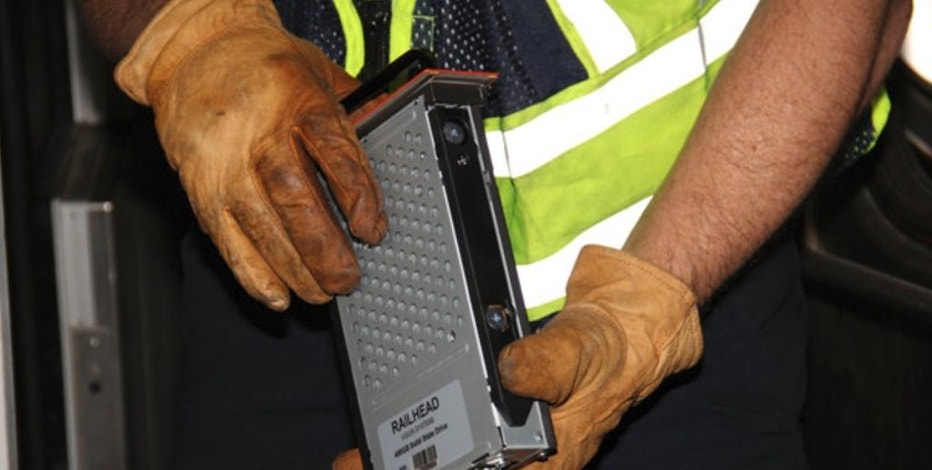 In this photo released by the National Transportation Safety Board (NTSB), a video recorder, recovered from the control cab of the lead car from N.J. Transit's Pascack Valley Line train No. 1614, is removed from the train as part of the National Transportation Safety Board's investigation, Tuesday, Oct. 4, 2016, in Hobokon, N.J., into last week's commuter train that slammed into the New Jersey rail station. Federal investigators recovered a data recorder, video recorder and the engineer's cellphone from the front car of the commuter train Tuesday afternoon and sent them to an agency lab for analysis. (N.J. Transit Police Det. Laquan Hudson/NTSB via AP)