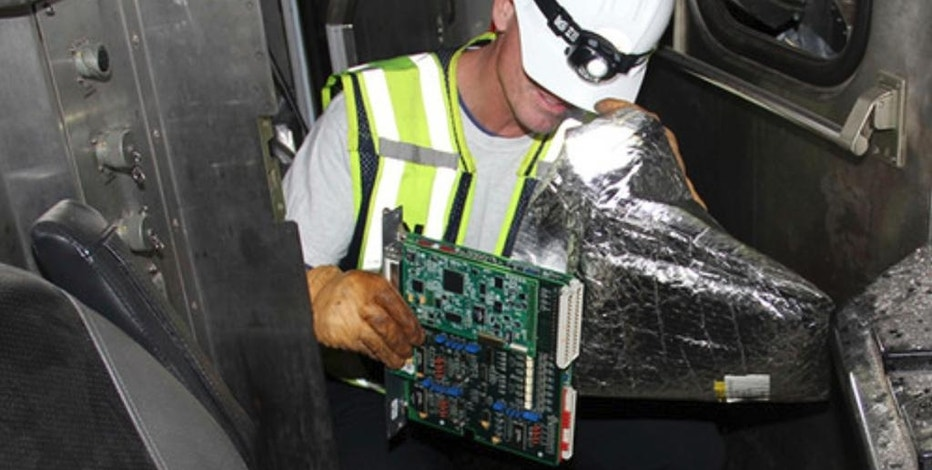 In this photo released by the National Transportation Safety Board (NTSB), National Transportation Safety Board investigator Michael Hiller places the event recorder,  recovered from the control cab of the lead car from N.J. Transit's Pascack Valley Line train No. 1614, into an anti static bag, Tuesday, Oct. 4, 2016, in Hobokon, N.J. Federal investigators recovered a data recorder, video recorder and the engineer's cellphone Tuesday from the commuter train that crashed into a New Jersey rail station last week. The items were sent to an agency lab for analysis.  (N.J. Transit Police Det. Laquan Hudson/NTSB via AP)