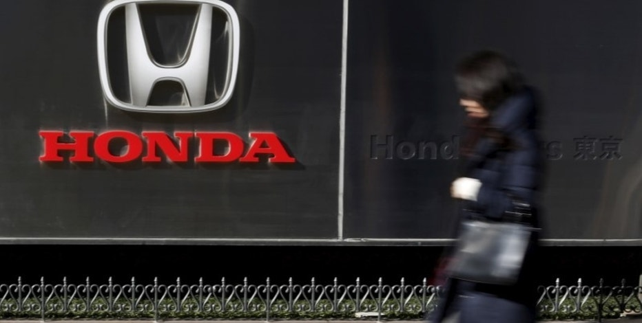 A woman walks past a logo of Honda Motor Co outside the company's dealership in Tokyo, Japan, January 27, 2016. REUTERS/Yuya Shino