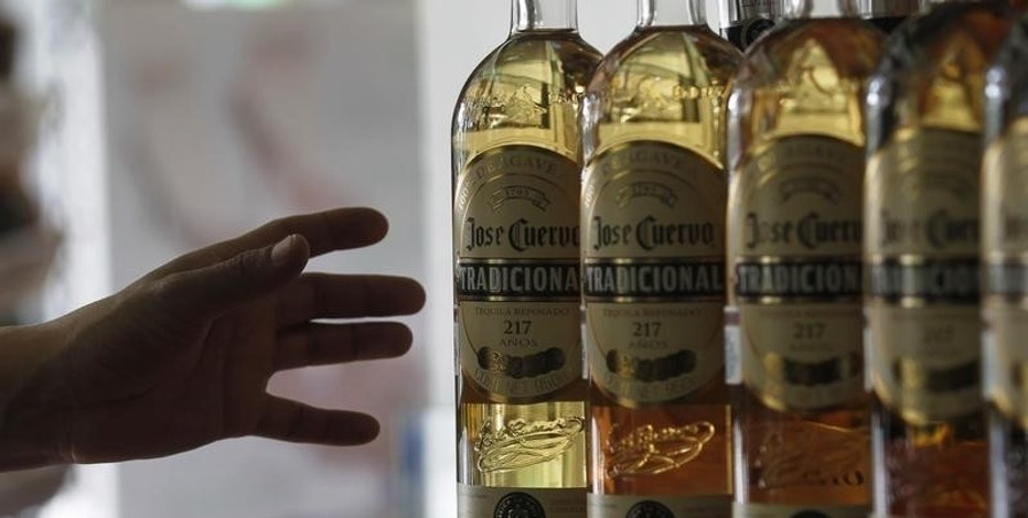 A man reaches for a bottle of Jose Cuervo Tequila in Mexico City December 11, 2012. REUTERS/Edgard Garrido