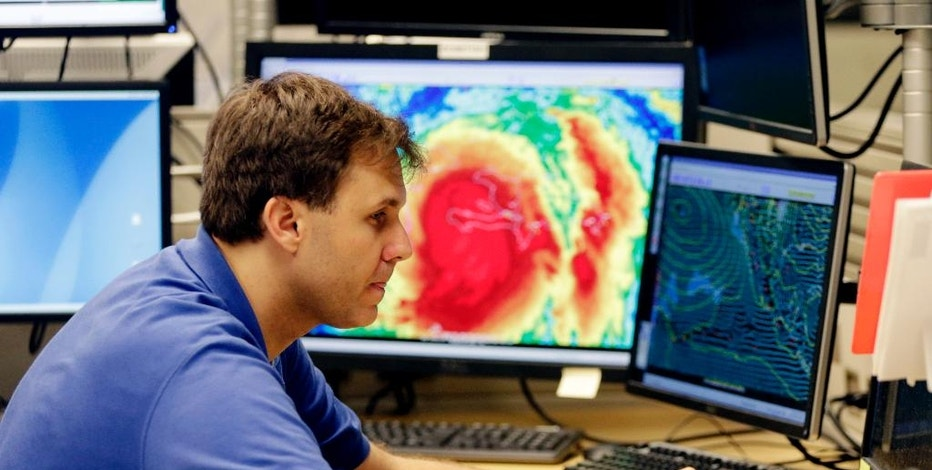 FILE - In this Tuesday, Oct. 4, 2016, file photo, hurricane specialist Eric Blake monitors the path of Hurricane Matthew at the National Hurricane Center, in Miami. Travelers along the East Coast are preparing for delays and cancellations as Hurricane Matthew heads toward the U.S. Airlines are preparing to suspend flights from Florida up through Georgia, South Carolina and North Carolina, depending on where the hurricane hits land. Cruise lines are shuffling ship itineraries and many frantic vacationers are looking at insurance policies to see if they are covered. (AP Photo/Lynne Sladky, File)