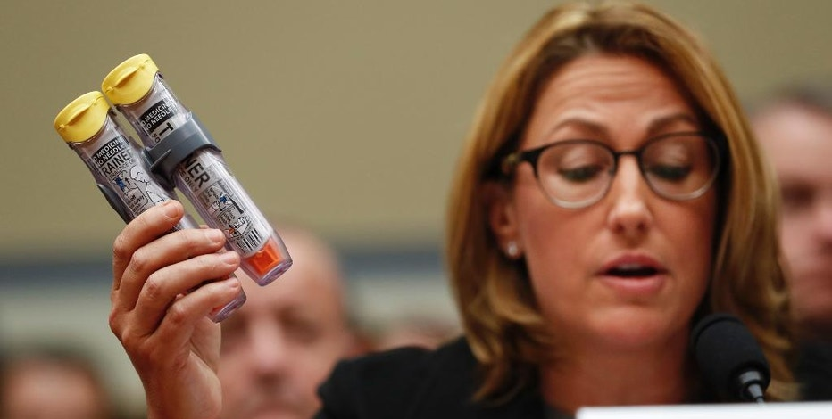 FILE - In this Wednesday, Sept. 21, 2016, file photo, Mylan CEO Heather Bresch holds up EpiPens while testifying on Capitol Hill in Washington, before the House Oversight Committee hearing on EpiPen price increases. Now the federal government, responding to Congressional inquiries, says EpiPen's maker has been overcharging Medicaid for years because the emergency shot is classified incorrectly as a generic medicine, so Mylan has been paying the government much-lower rebates off the price than it should. (AP Photo/Pablo Martinez Monsivais, File)