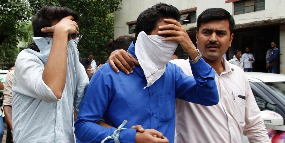 A police official, right, escorts two men outside the court in Thane, outskirts of Mumbai, India, Thursday, Oct. 6, 2016. Indian police have arrested 70 people and are questioning hundreds more after uncovering a massive scam to cheat thousands of Americans out of millions of dollars by posing as U.S. tax authorities and demanding unpaid taxes. (AP Photo/Rajanish Kakade)