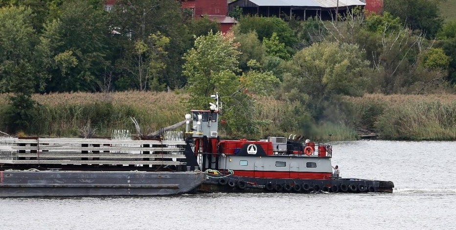 In this Wednesday, Sept. 28, 2016 photo, a tugboat and barge travel south on the Hudson River in Stuyvesant, N.Y. A group of citizens, lawmakers and environmentalists is fighting a proposal to establish more than 40 commercial anchorages at locations along a stretch of the Hudson River running north from New York City. Shipping industry officials said they need safe places to anchor, sometimes for days, barges hauling North Dakota crude oil to East Coast refineries and export terminals. (AP Photo/Mike Groll)