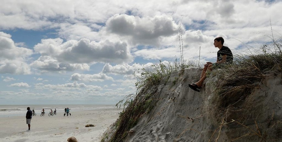 A boy sits on a cliff formed by erosion from Hurricane Matthew on the beach at Jacksonville Beach, Fla. Saturday, Oct. 8, 2016. The fast-weakening storm continued its march along the Atlantic coast Saturday. (AP Photo/Charlie Riedel)