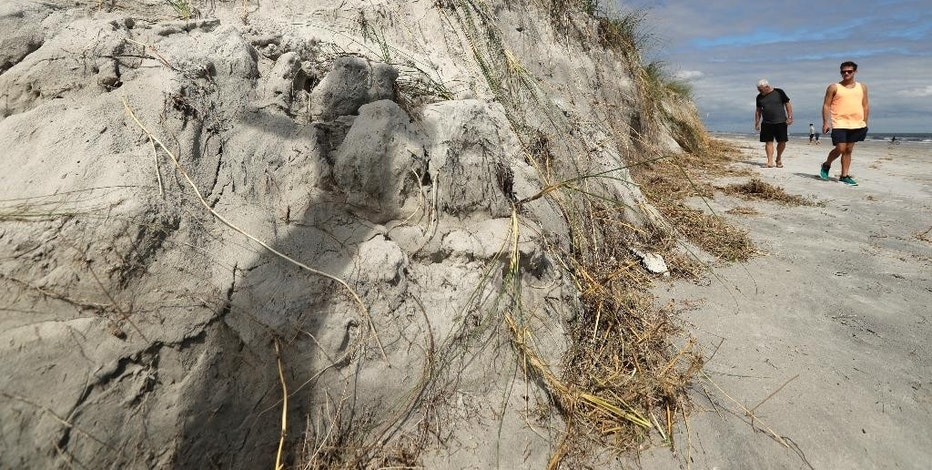 People look at a cliff formed by erosion from Hurricane Matthew on the beach at Jacksonville Beach, Fla. Saturday, Oct. 8, 2016. The fast-weakening storm continued its march along the Atlantic coast Saturday. (AP Photo/Charlie Riedel)
