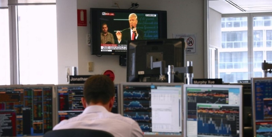 A trader works at his desk as the U.S. presidential town hall debate between Republican presidential nominee Donald Trump and Democratic nominee Hillary Clinton is shown on television at Citibank's trading floor located in central Sydney, Australia, October 10, 2016.      REUTERS/David Gray