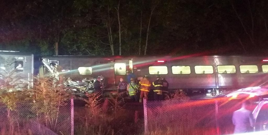 In this photo provided by Sarah Qamar rescue personnel look at a Long Island Railroad train that derailed near New Hyde Park, N.Y., Saturday, Oct. 8, 2016.  The commuter train derailed east of New York City after it hit a work train on the tracks. A spokesman for the Long Island Rail Road says the eastbound train derailed east of New Hyde Park just after 9 p.m. Saturday. A spokeswoman for the Nassau County Police Department says there are 50 to 100 injuries, none of them life-threatening. (Sarah Qamar via AP)
