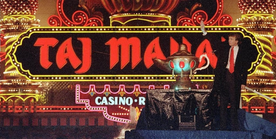 """FILE - In this April 5, 1990 file photo, Donald Trump stands next to a genie's lamp as the lights of his Trump Taj Mahal Casino Resort light up during ceremonies to mark its opening in Atlantic City, N.J. Trump opened his Trump Taj Mahal casino 26 years ago, calling it """"the eighth wonder of the world."""" But his friend and fellow billionaire Carl Icahn is closing it Monday morning, making it the fifth casualty of Atlantic City's casino crisis. (AP Photo/Mike Derer, File)"""