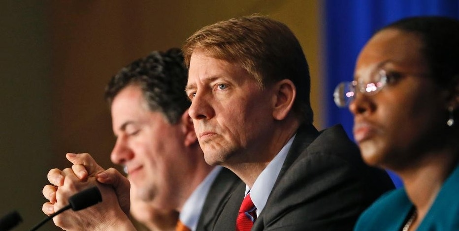 FILE - In this Thursday, March 26, 2015, file photo, Consumer Financial Protection Bureau Director Richard Cordray, center, listens to comments during a panel discussion in Richmond, Va. On Tuesday, Oct. 11, 2016, a federal appeals court ruled that the way the CFPB is organized violates the Constitution's separation of powers by limiting the president's ability to remove the director who heads the agency. Cordray, a Democrat and former Ohio attorney general, has run the agency since it began operating in July 2011. (AP Photo/Steve Helber, File)