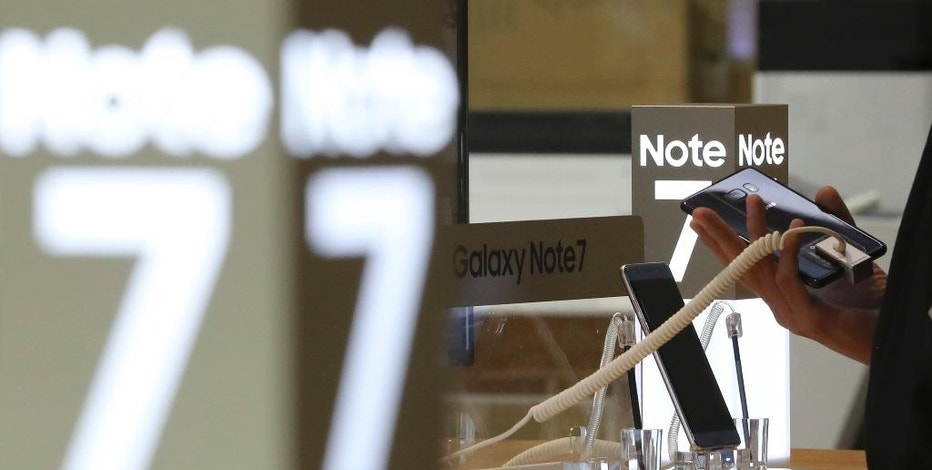 A visitor tries the Samsung Electronics Galaxy Note 7 smartphone at its shop in Seoul, South Korea, Tuesday, Oct. 11, 2016. Samsung said Tuesday it is halting sales of the star-crossed Galaxy Note 7 smartphone after a spate of fires involving new devices that were supposed to be safe replacements for recalled models. (AP Photo/Lee Jin-man)