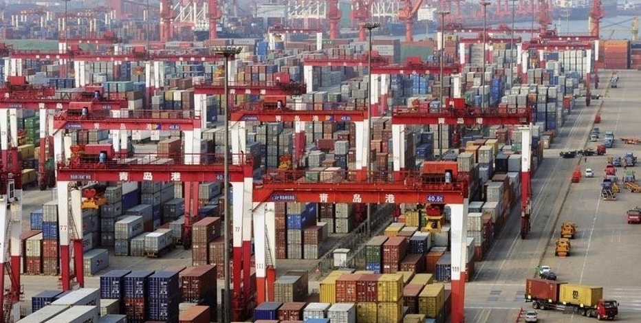 Trucks drive past piles of shipping containers at the Qingdao port in Qingdao, Shandong province June 8, 2014. REUTERS/China Stringer Network