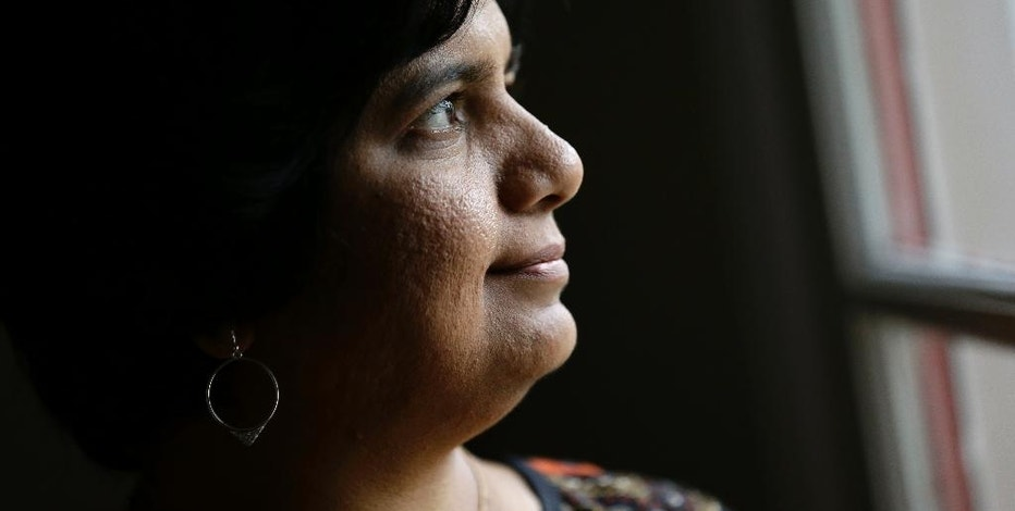 In this Friday, Sept. 16, 2016, photo, Manasi Gopala, a software developer in North Carolina's Research Triangle, peers out of her back door in Cary, N.C. She left her birthplace of Bangalore, India in 2002, even as many Americans lamented the outsourcing of tech jobs to that city. Gopala arrived in the United States on a marriage visa and promptly obtained a master's degree in computer engineering. She became a citizen in 2013. (AP Photo/Gerry Broome)