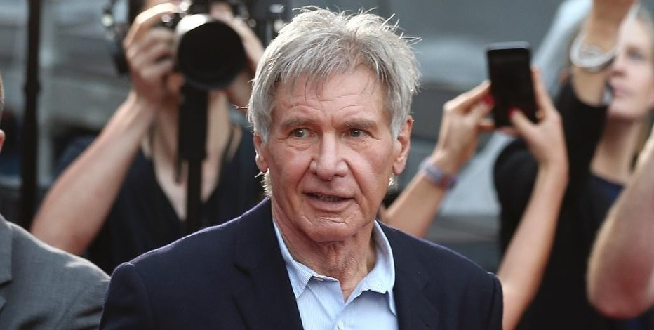 """FILE - In this December 10, 2015 file photo, Harrison Ford greets fans during a Star Wars fan event in Sydney. A film production company has been fined 1.6 million pounds ($1.95 million) over an accident on the set of """"Star Wars: The Force Awakens"""" that broke the leg of star Harrison Ford. The actor was struck by a hydraulic door on the set of the Millennium Falcon — his character Han Solo's spaceship — at Pinewood Studios near London in June 2014. A judge at Aylesbury Crown Court north of London said Wednesday, Oct. 12, 2016 that Foodles Production (UK) Ltd. should have informed Ford of the risks.(AP Photo/Rob Griffith, File)"""