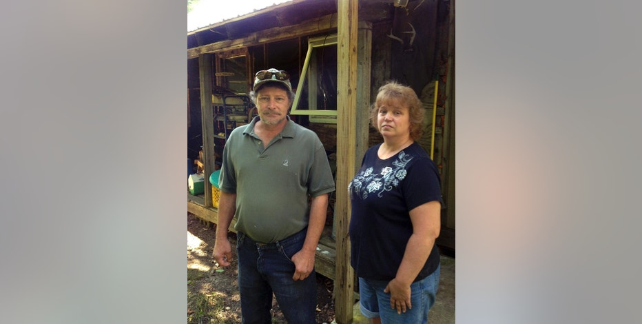In this Sept. 7, 2016 photo, Steve and Luann Therrien stand outside their former home in Sheffield, Vt., where wind power turbines are installed. Once it was just another cabin on a Vermont hillside. Now it's an emblem in the debate over noise from the growing wind energy industry. Studies have repeatedly found no evidence connecting noise from wind power turbines to human health problems. But critics question the soundness of those studies. Among them are Steve and Luann Therrien, who say the wind farm near their home made their lives hell. (AP Photo/Dave Gram)