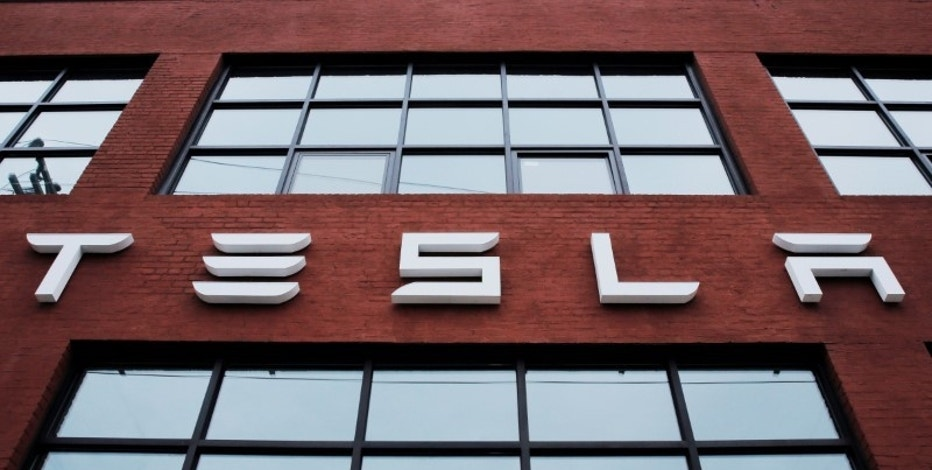 A Tesla logo hangs on a building outside of a Tesla dealership in New York, U.S., April 29, 2016. REUTERS/Lucas Jackson/File Photo