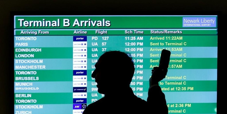 FILE - In this Wednesday, Nov. 27, 2013, file photo, a person points to a screen with an airplane travel list while holding up a phone at Newark Liberty International Airport, in Newark, N.J. Some airlines are taking extra steps to prevent a disaster in case a passenger's device powered by a lithium ion battery catches fire during flight. At least three U.S. airlines are adding new fire-suppression equipment to fleets in case a cellphone or laptop battery overheats, catches on fire and can't be extinguished. (AP Photo/Julio Cortez, File)