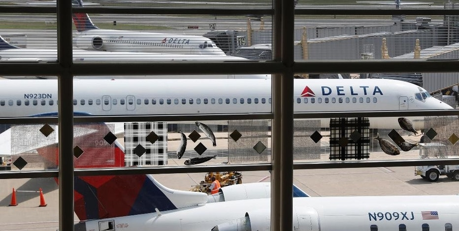 FILE - In this Monday, Aug. 8, 2016, file photo, Delta Air Lines planes are parked at Ronald Reagan Washington National Airport, in Washington. Delta Air Lines reports financial results Thursday, Oct. 13, 2016. (AP Photo/Carolyn Kaster, File)