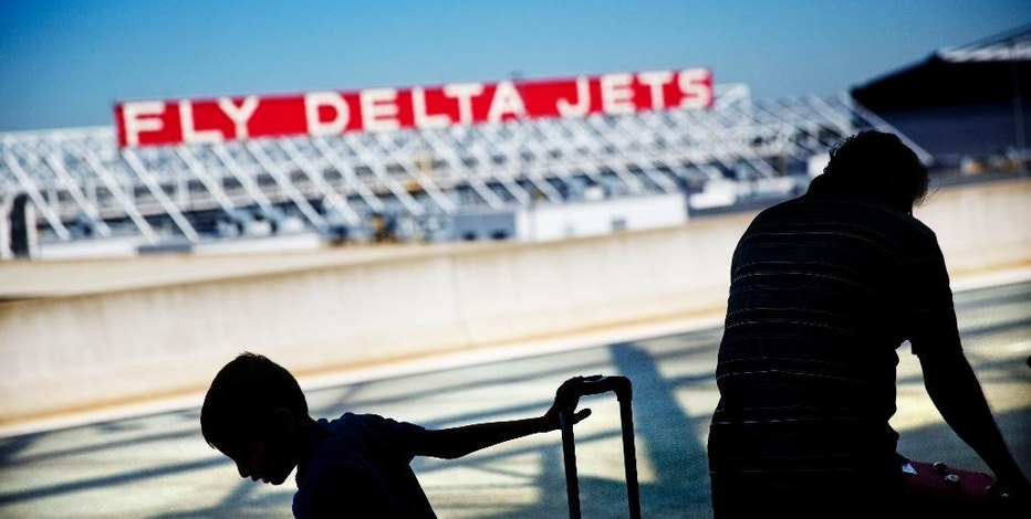 Passengers unload in front of a Delta Air Lines sign at Hartsfield-Jackson Atlanta International Airport, in Atlanta, Thursday, Oct. 13, 2016. Lower airfares and rising salaries are putting a squeeze on Delta Air Lines. Luckily for the airline, the price of jet fuel remains cheap and the Atlanta-based carrier was able to report a third-quarter profit of $1.26 billion, down 4 percent from the same period a year earlier. (AP Photo/David Goldman)