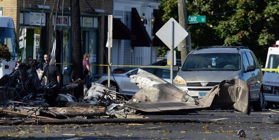 The remains of a small plane are seen along Main St, Wednesday, Oct. 12, 2016, in East Hartford, Conn., a day following the plane's crash. The FBI is taking over as lead investigator in the deadly crash of a small plane carrying a flight instructor and a student pilot because of indications that it might have been a criminal act, safety officials said Wednesday. (AP Photo/Jessica Hill)