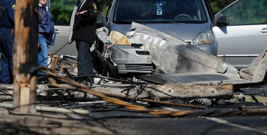 Investigators look at a snapped off telephone pole next to the remains of a small plane along Main St, Wednesday, Oct. 12, 2016, in East Hartford, Conn., a day following the plane's crash. The FBI is taking over as lead investigator in the deadly crash of a small plane carrying a flight instructor and a student pilot because of indications that it might have been a criminal act, safety officials said Wednesday. (AP Photo/Jessica Hill)