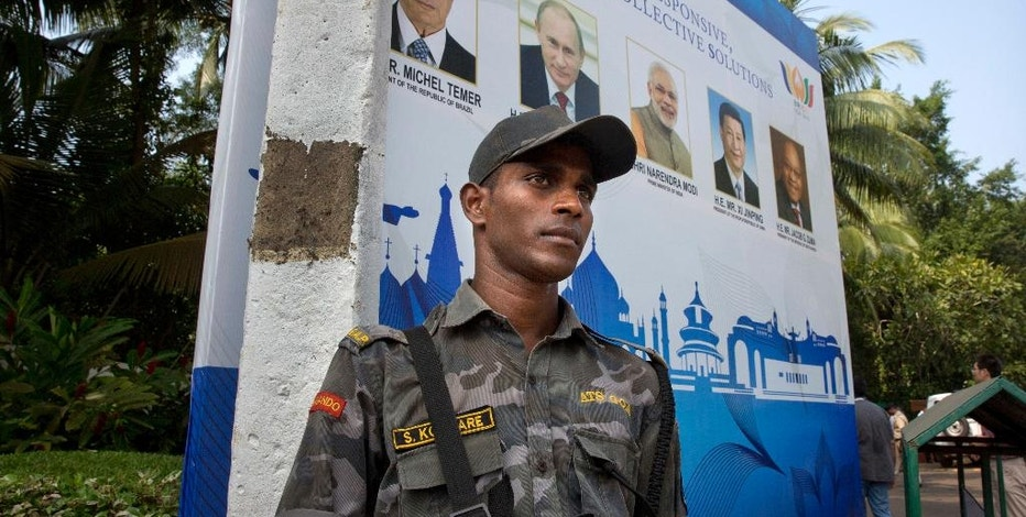 A Goa police commander stands guard near the banner of BRICS summit in Goa, India, Friday, Oct. 14, 2016. The leaders of five big developing nations that banded together in 2009 as the so-called BRICS nations, are set to attend their annual summit Oct. 15-16, 2016 in a beach resort town in the western Indian state of Goa. But with their own economies now flagging, some analysts are questioning whether the group, consisting of Brazil, Russia, India, China and South Africa, still has clout in representing nearly half the world's population and a quarter of its economy at $16.6 trillion. (AP Photo/Manish Swarup)