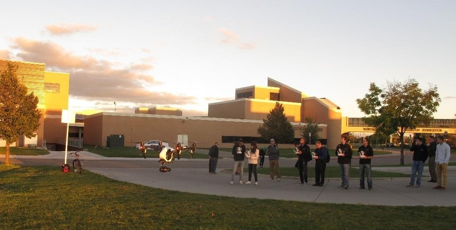 In this Sept. 28, 2016 photo, students in the first unmanned aircraft business class at the University of North Dakota fly a drone outside the school. In addition to learning how to fly the aircraft, the students are receiving real-world business experience and will end the semester by presenting their ideas for a business to executives.There are 24 students in the inaugural class that is part of the college's business school. (AP Photo/Dave Kolpack)