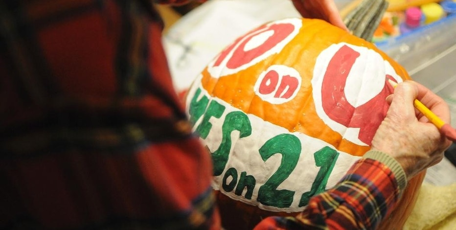 In this Wednesday, Oct. 12, 2016, photo, Cathy Brechtelsbauer, a supporter of a ballot measure that would cap short-term lenders' interest rates in South Dakota, decorates a pumpkin for the campaign in Sioux Falls, S.D. Short-term lenders say the passage of a ballot measure capping payday loan interest rates would destroy the industry in South Dakota. (AP Photo/James Nord)