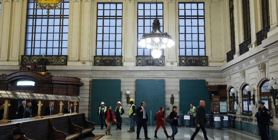 FILE - In this Monday, Oct. 10, 2016, photo, commuters walk past boarded up track entrances at Hoboken Terminal in Hoboken, N.J., after the Sept. 29 commuter train crash. New Jersey Transit has said six more tracks will open at 4 a.m. Monday, Oct. 17, at Hoboken Terminal, which has resumed its operations on Oct. 10. It also noted that the station's ticket office has resumed operations. (AP Photo/Seth Wenig, File)