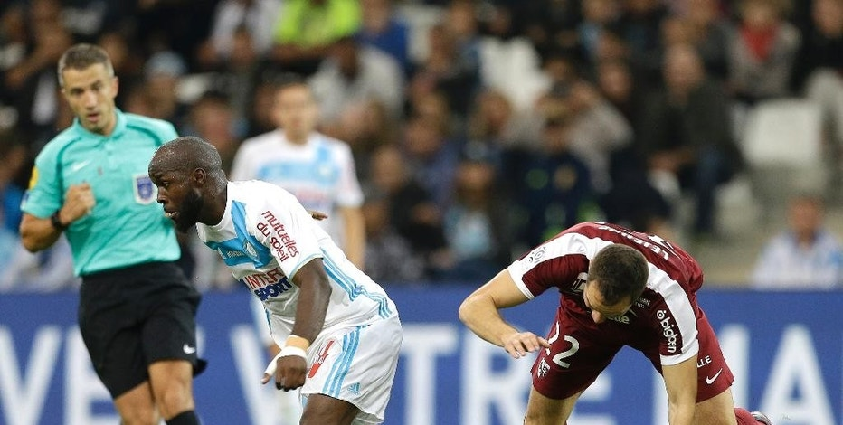 Marseille's Lassana Diarra, left, challenges for the ball with Metz's Kevin Lejeune during the French League One soccer match between Marseille and Metz, at the Velodrome Stadium, in Marseille, southern France, Sunday, Oct. 16, 2016. (AP Photo/Claude Paris)