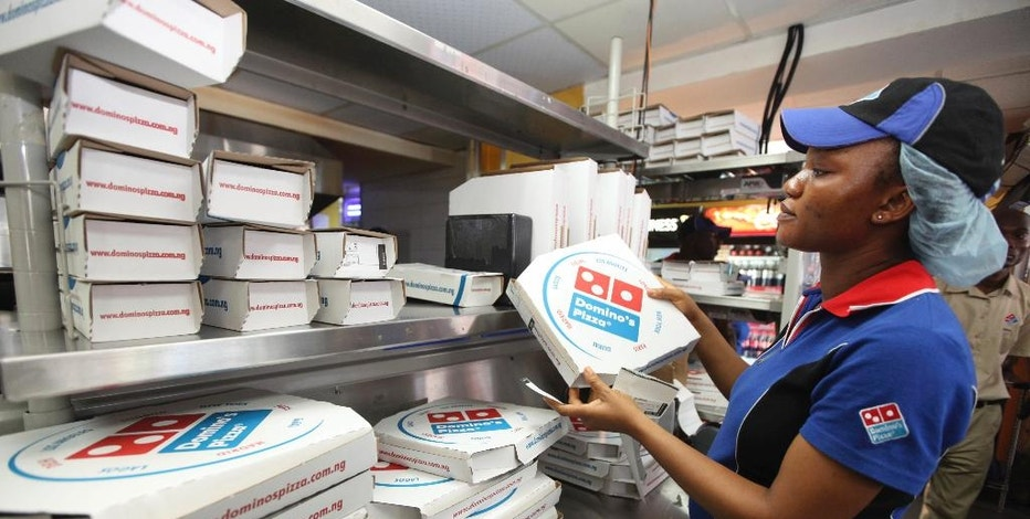 FILE - In this Sunday, Feb. 10, 2013, file photo, a worker prepares boxes at a Domino's pizza restaurant in Lagos, Nigeria. Domino's reports financial results Tuesday, Oct. 18, 2016. ( AP Photo/Sunday Alamba, File)