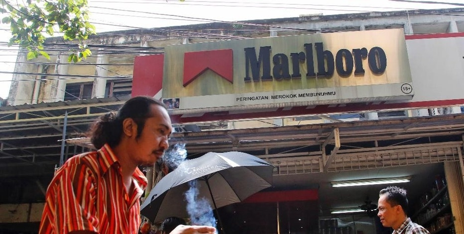 FILE - In this Feb. 5, 2015, file photo, a man smokes a cigarette as he walks past a shop displaying a Marlboro sign at a market in Jakarta, Indonesia. Philip Morris International reports financial results Tuesday, Oct. 18, 2016. (AP Photo/Dita Alangkara, File)