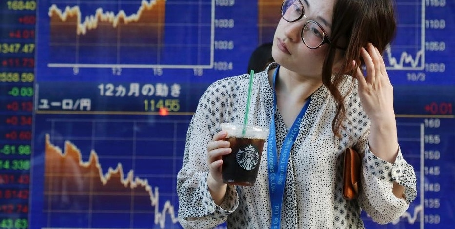 A woman stands in front of an electronic stock board of a securities firm in Tokyo, Tuesday, Oct. 18, 2016. Asian stock markets rose Tuesday ahead of China's release of quarterly growth data and a policy meeting of the European Central Bank later in the week. (AP Photo/Koji Sasahara)