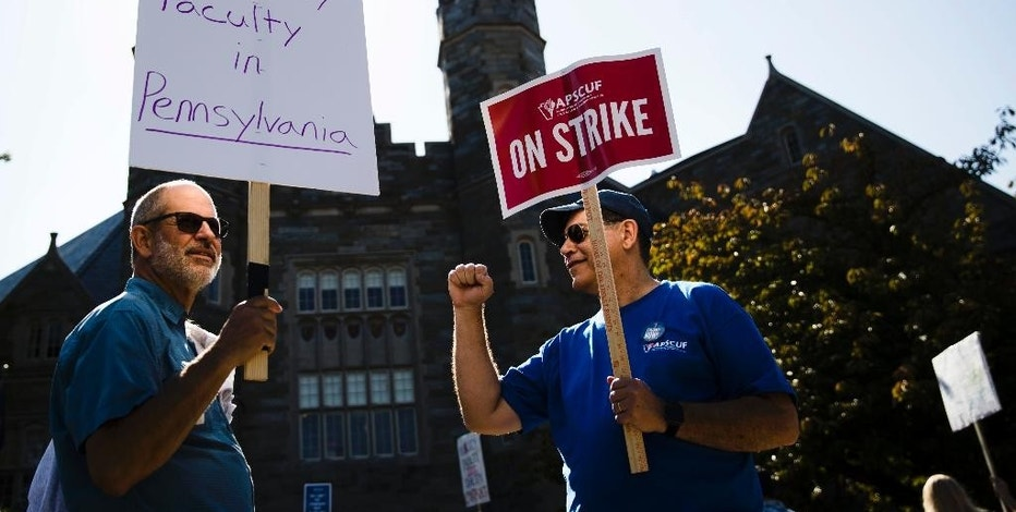 Faculty members Chuck Shorten, left, and Brent Thompson picket at West Chester University in West Chester, Pa, Wednesday, Oct. 19, 2016. Faculty at Pennsylvania state universities went on strike Wednesday morning after contract negotiations between the Pennsylvania State System of Higher Education and its faculty union hit an impasse. (AP Photo/Matt Rourke)