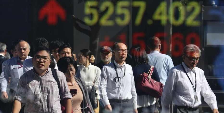 People are reflected on the electronic board of a securities firm in Tokyo, Monday, Oct. 24, 2016. Asian markets mostly rose Monday as Japan reported its trade balance swung to a surplus in September and strong Japanese manufacturing data from a purchasing manager's survey also suggested signs of improved activity in the world's third biggest economy. Attention is likely to focus this week on U.S. growth data. (AP Photo/Koji Sasahara)