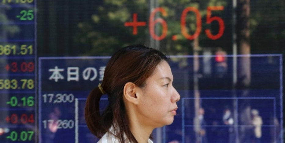 A woman walks by an electronic stock board of a securities firm in Tokyo, Monday, Oct. 24, 2016. Asian markets mostly rose Monday as Japan reported its trade balance swung to a surplus in September and strong Japanese manufacturing data from a purchasing manager's survey also suggested signs of improved activity in the world's third biggest economy. Attention is likely to focus this week on U.S. growth data. (AP Photo/Koji Sasahara)