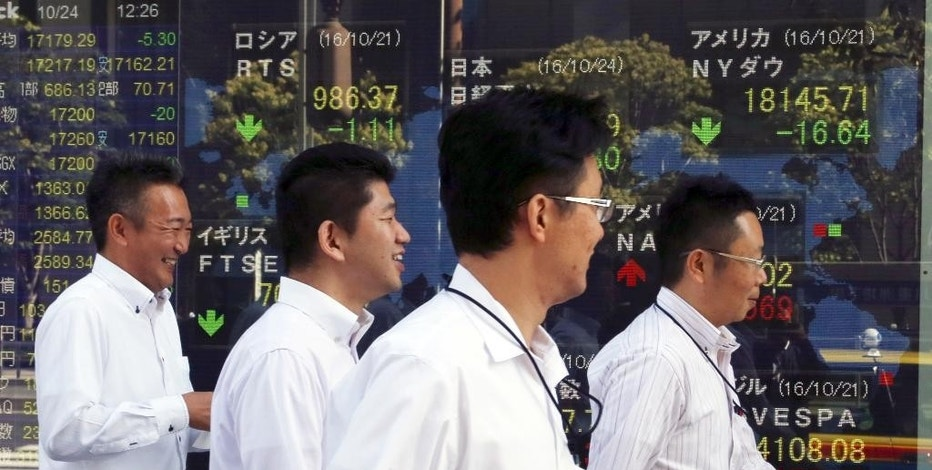 People walk by an electronic stock board of a securities firm in Tokyo, Monday, Oct. 24, 2016. Asian markets mostly rose Monday as Japan reported its trade balance swung to a surplus in September and strong Japanese manufacturing data from a purchasing manager's survey also suggested signs of improved activity in the world's third biggest economy. Attention is likely to focus this week on U.S. growth data. (AP Photo/Koji Sasahara)
