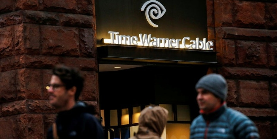 People pass by a Time Warner Cable branch in the Manhattan borough in New York, U.S., October 22, 2016. REUTERS/Eduardo Munoz