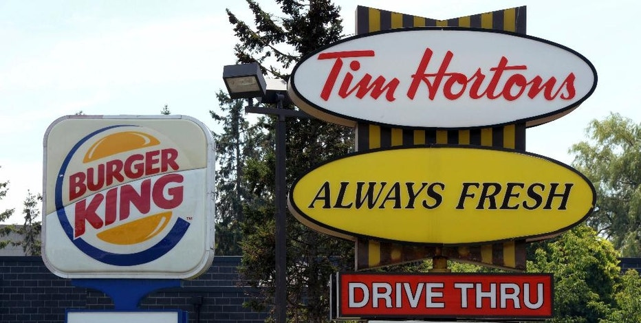 FILE - This Aug. 25, 2014, file photo, shows signs for Burger King and Tim Hortons locations in Ottawa, Ontario. Restaurant Brands International, the parent company of Burger King and Tim Hortons, reports financial results on Monday, Oct. 24, 2016. (Sean Kilpatrick/The Canadian Press via AP, File)