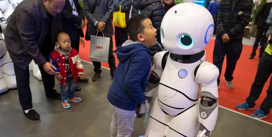 "In this Friday, Oct. 21, 2016 photo, a Chinese boy shouts into the Canbot, a companion robot, displayed during the World Robot Conference in Beijing, China. China is showcasing its burgeoning robot industry as it seeks to promote use of more advanced technologies in Chinese factories and create high-end products that redefine the meaning of ""Made in China."" The Canbot can dance and respond to voice commands, while others can play badminton, sand cell phone cases and sort computer chips. (AP Photo/Ng Han Guan)"